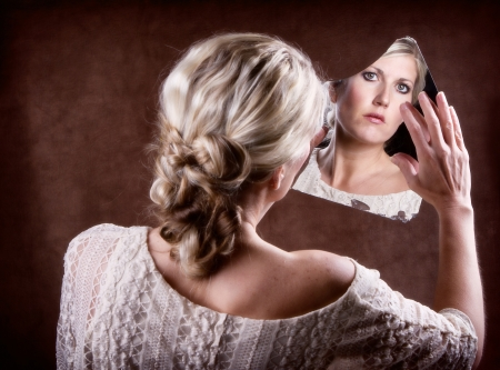 Woman looking into a broken mirror touching it with her hand, with back of head showing