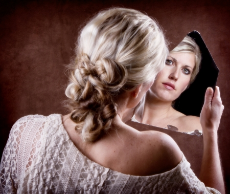 Woman looking into a broken mirror with back of head showing photo