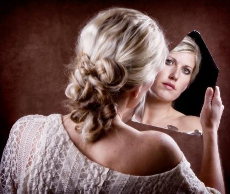 broken back: Woman looking into a broken mirror with back of head showing