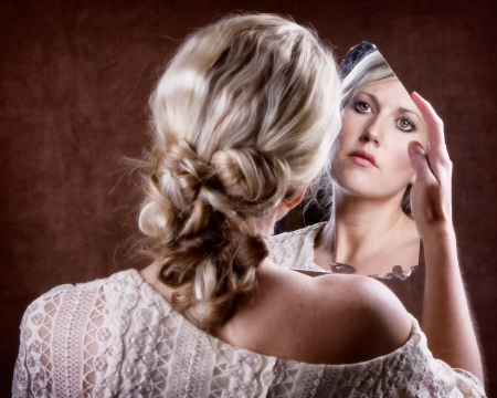Woman looking into a broken mirror with a sad look,  back of head showing