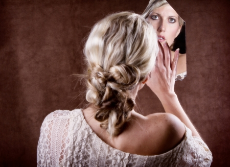Woman looking into a broken mirror touching it with her hand, with back of head showing photo