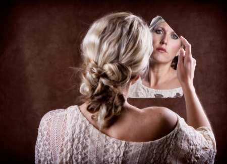 Woman looking into a broken mirror with a sad look,  back of head showing photo