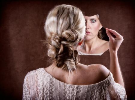 mirar espejo: Mujer que mira en un espejo roto con la parte posterior de la cabeza que muestra Foto de archivo