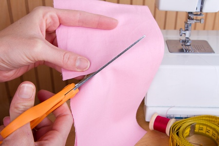 Cutting out a piece of pink fabric with scissors, sewing machine in background photo