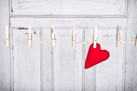 Red heart on a clothes line with a weathered white vintage panel in the background photo