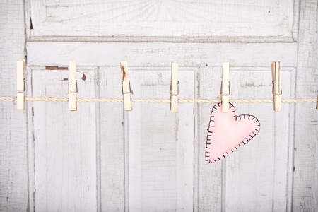 Pink heart on a clothes line with a weathered white vintage panel in the background photo