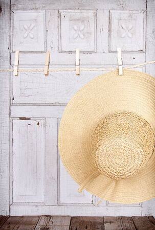 Sun hat hanging froma clothes line with a wooden antique panel for background photo