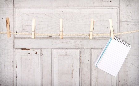 clothespin: Note pad hanging from a clothes line with an antique wooden background