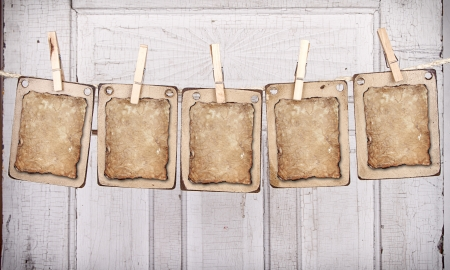 Aged wooden rectangles with aged paper on a clothes line ready for copy photo
