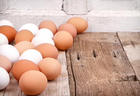 Brown and white eggs on a rustic wooden plank  Foto de archivo