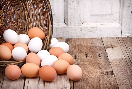 Brown and white eggs spilling out of a wicker basket onto a rustic wooden plank Banco de Imagens