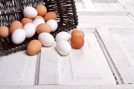 Brown eggs spilling out of a wicker basket onto an antique wooden panel photo