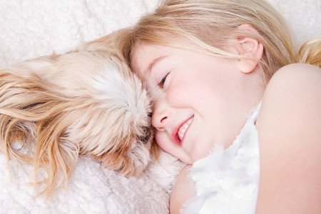 shih tzu: Young girl or child laying with a shih tzu dog