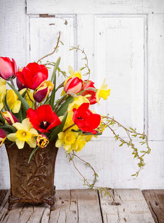 floral arrangements: Spring flowers tulips and daffodils in a vase on a white wooden background
