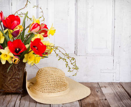 Spring flowers tulips and daffodils  with a straw sun hat on a white antique wooden background photo