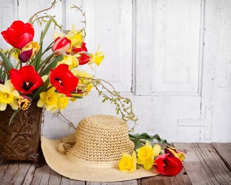 chapeau de paille: Fleurs de printemps des tulipes et des jonquilles avec un chapeau de soleil de paille sur un fond en bois blanc antique Banque d'images