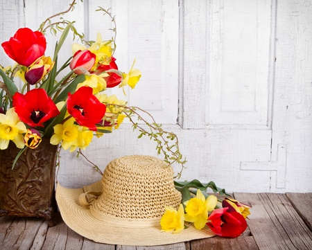 tulips in vase: Spring flowers tulips and daffodils  with a straw sun hat on a white antique wooden background