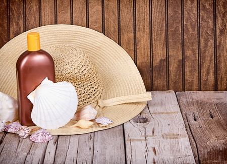 sun lotion: Sun hat and sun lotion with shells on wooden background Stock Photo