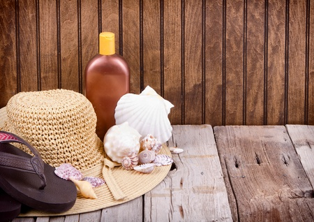 Sun hat, sandals and sun lotion with shells on wooden background photo
