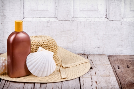 Sun hat and sun lotion with shells on wooden background photo
