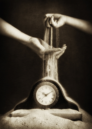 Childs hand passing sand to an adults hand dropping sand onto a clock covered in sand