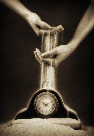 sand timer: hands holding sand flowing down on a clock covered in sand