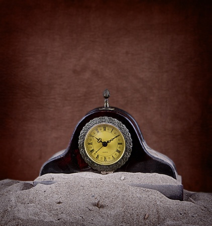 An antique clock covered in sand with a brown background
