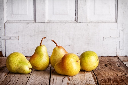 Group of Pears on wooden planks with a white antique background