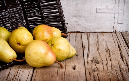 Pears spilling out of a black wicker basket onto rustic wooden planks, white vintage or antique background Foto de archivo