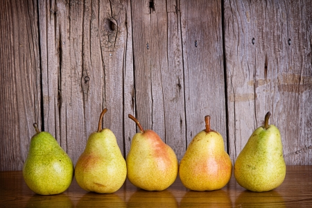 Pears lined up in a row on a rustic wooden background