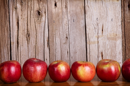 Apples lined up in a row against a white rustic or vintage background photo
