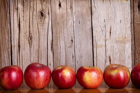 mela rossa: Mele allineati in una riga su uno sfondo bianco rustico o d'epoca