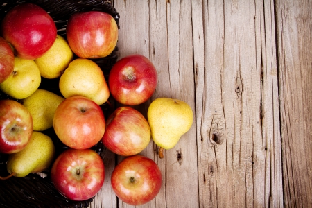 apples and pears spilling out of a basket onto a rustic wooden plank Foto de archivo