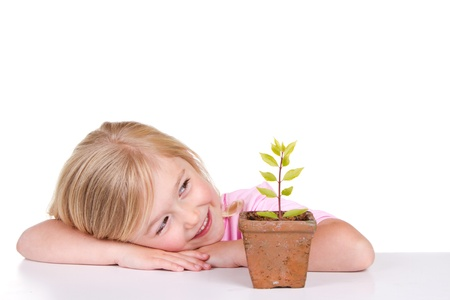 Young girl or child with a potted plant while smiling, isolated on white
