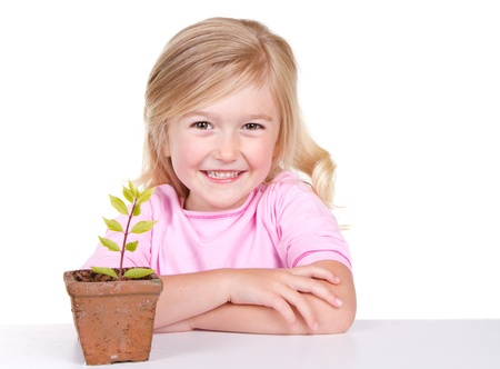 Young girl or child with a potted plant while smiling, isolated on white  photo