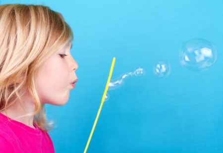 Child or girl blowing bubbles on a blue background photo