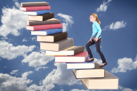 Child or girl climbing a staircase of books on cloudy sky background