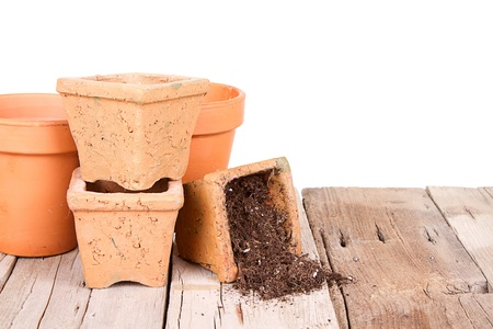 Terracotta or clay gardening pots with dirt spilling out of a pot, on a wooden plank with a background photo