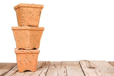 Terracotta or clay gardening pots stacked on a wooden plank on a white background