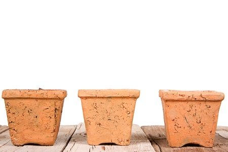 Terracotta or clay gardening pots on a wooden plank on a white background photo