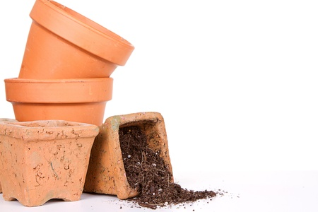 unused: Terracotta or clay gardening pots with dirt spilling out of a pot, on a white background