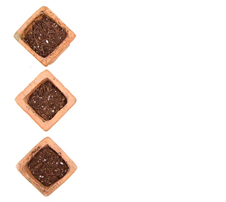 Terracotta or clay gardening pots with dirt on a white background