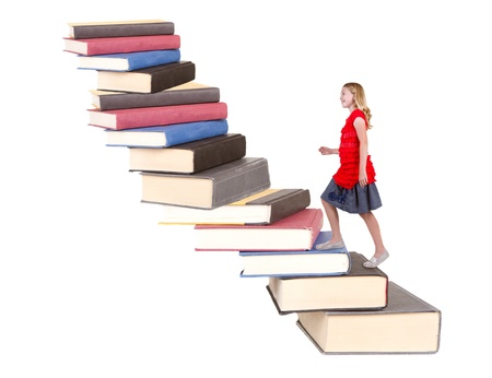 pre teen girl: young teenage girl climbing a stair case made of books  isolated white background Stock Photo