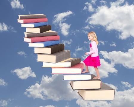 niño escalando: niño joven que sube una escalera de libros con un fondo nublado Foto de archivo