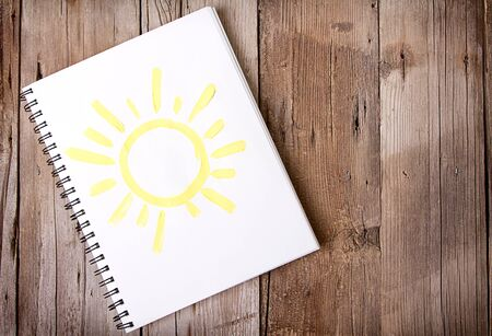 Painting of sun on notebook or sketch book with wooden planks for background