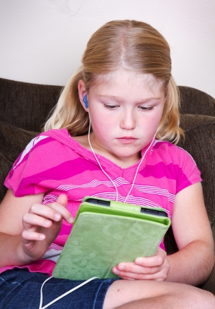 Child using a tablet with headphones while sitting on a couch Banco de Imagens