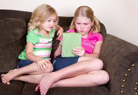 sofa: Children or sisters using a tablet while sitting on couch