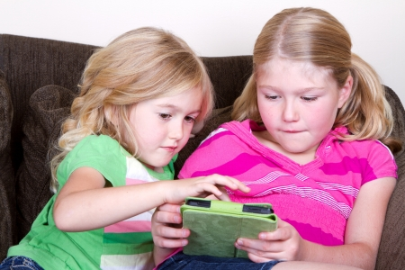 Children or sisters using a tablet while sitting on couch photo
