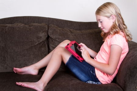 Teen using tablet while sitting or relaxing on couch Stock Photo