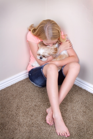 sadness: Sad teen in corner holding her shih tzu dog for comfort Stock Photo